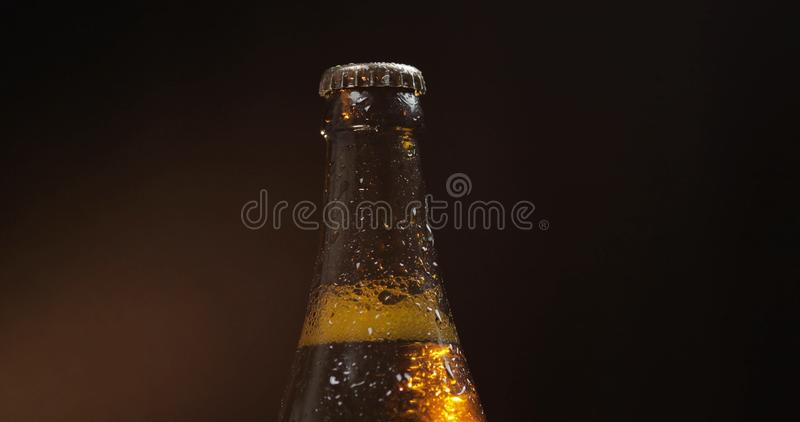 Bottle of cold beer on a black background. Condensate stock photos