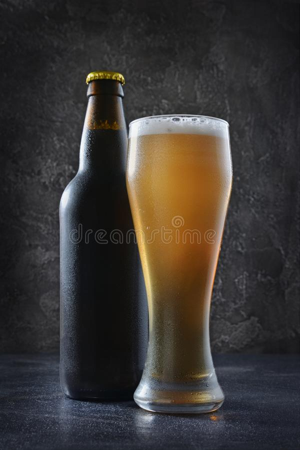 Bottle of cold beer and glass with foam. On dark gray concrete background stock photography