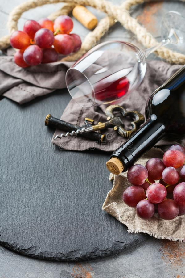 Bottle, corkscrew, glass of red wine, grapes on a table. Food and drink, still life, holidays seasonal harvesting fall autumn concept. Bottle, corkscrew, corks stock photo