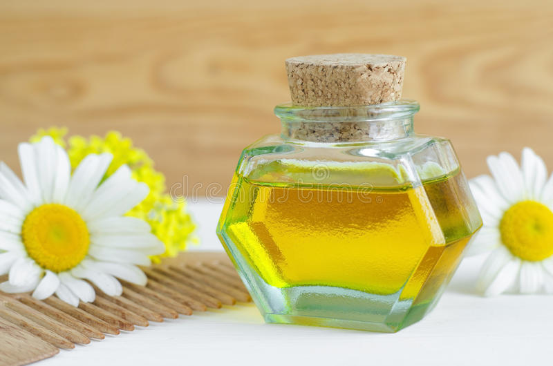 Bottle of cosmetic chamomile oil and wooden hair comb. Small bottle of cosmetic chamomile oil and wooden hair comb stock image