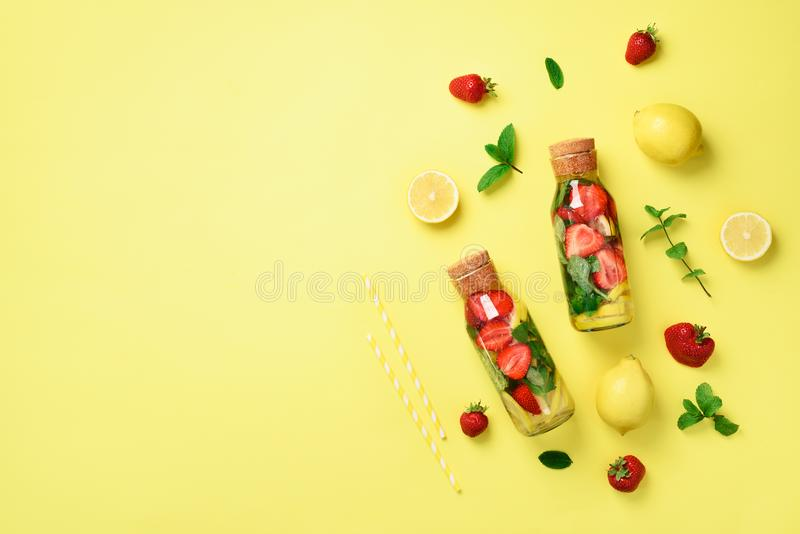 Bottle of detox water with mint, lemon, strawberry on yellow background. Flat lay. Citrus lemonade. Summer fruit infused royalty free stock photos