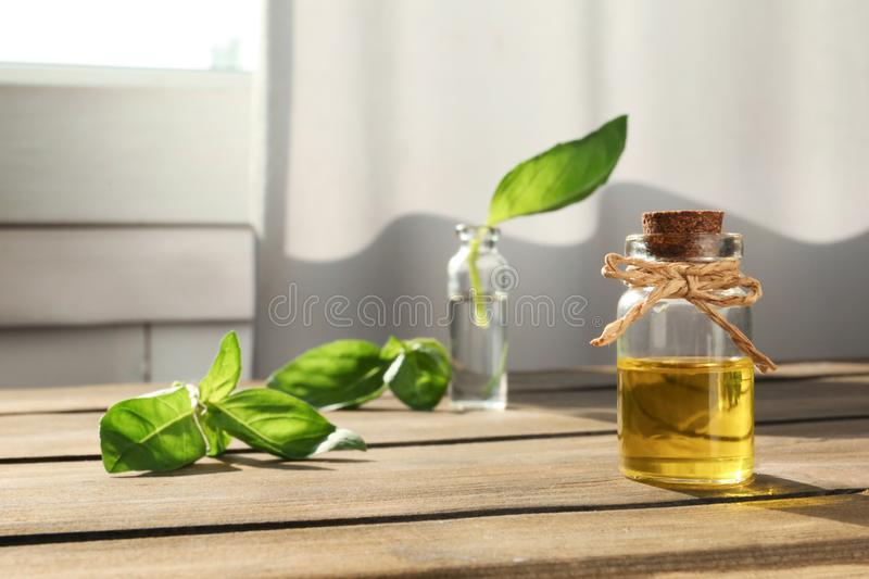 Bottle of essential basil oil on table against blurred background. stock image