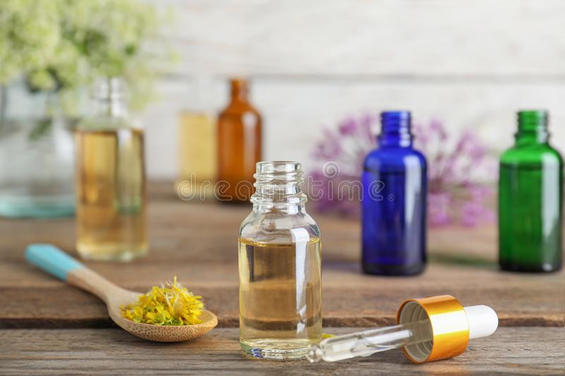Bottle of essential oil, pipette and spoon with flowers on wooden table royalty free stock photo