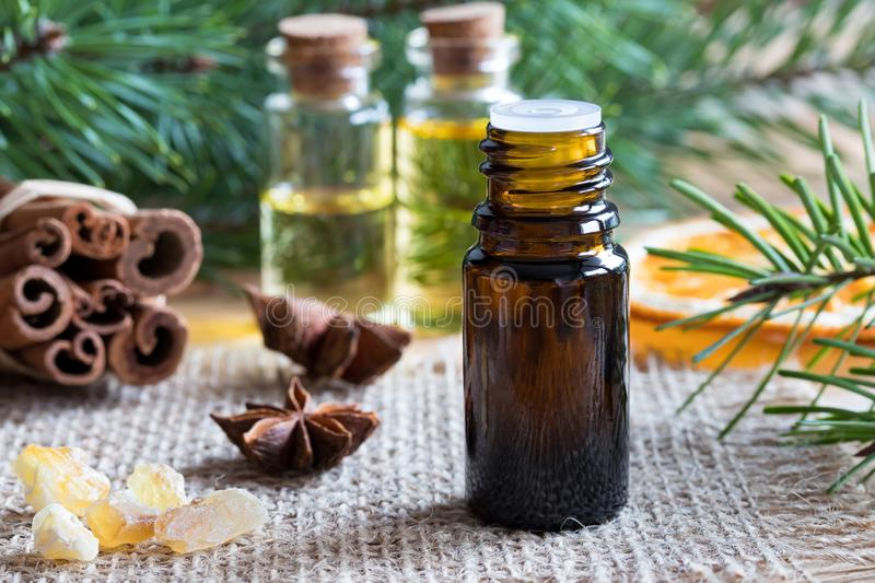 A bottle of essential oil with star anise, cinnamon, frankincense, dried orange, pine and fir branches stock images