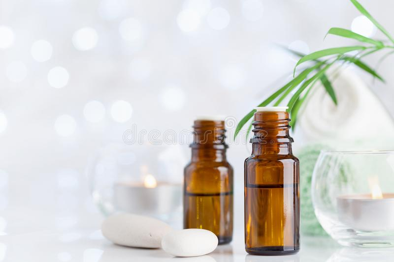 Bottle with essential oil, towel and candles on white table. Spa, aromatherapy, wellness, beauty background. royalty free stock image