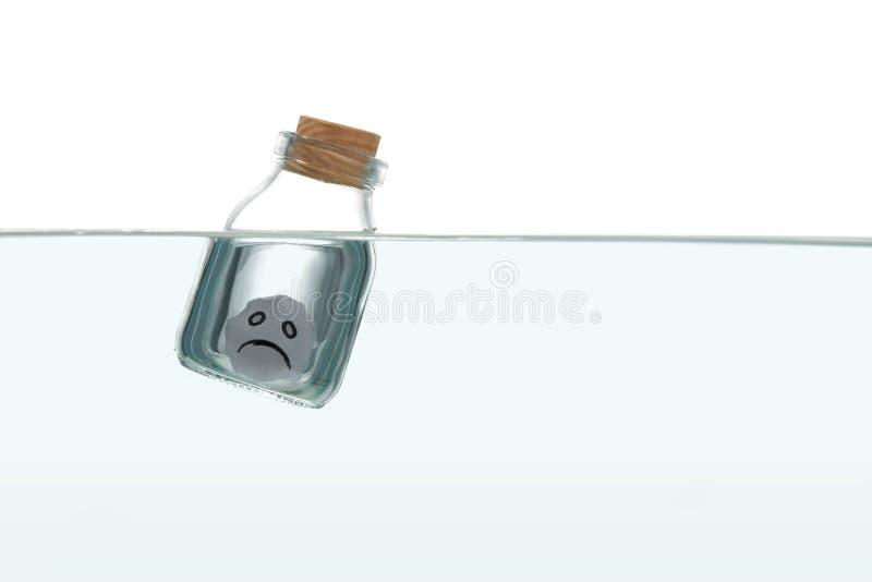 Sad face inside a bottle in water