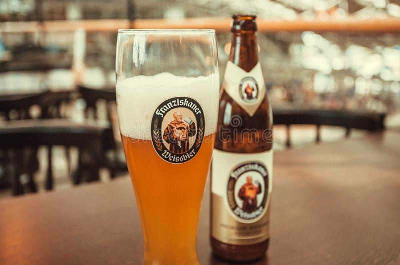 Bottle of german beer Franziskaner Weissbier with bright color and glass on restaurant table stock photo