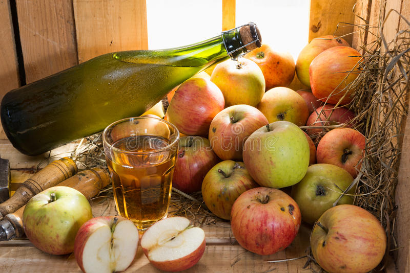 Bottle and glass of cider with apples. In a old barn royalty free stock photo