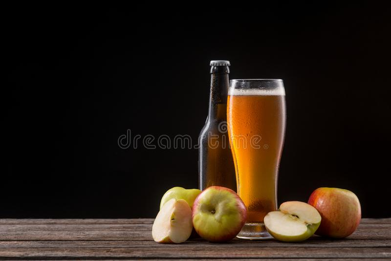 Bottle and glass of cider. Unopened bottle and glass of cider. Pieces and whole apples, the main ingredient of this sweet alcoholic beverage. Big empty space in stock images