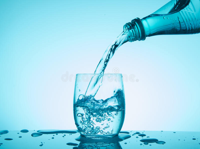 Bottle and glass with creative splashing water on blue background royalty free stock photo