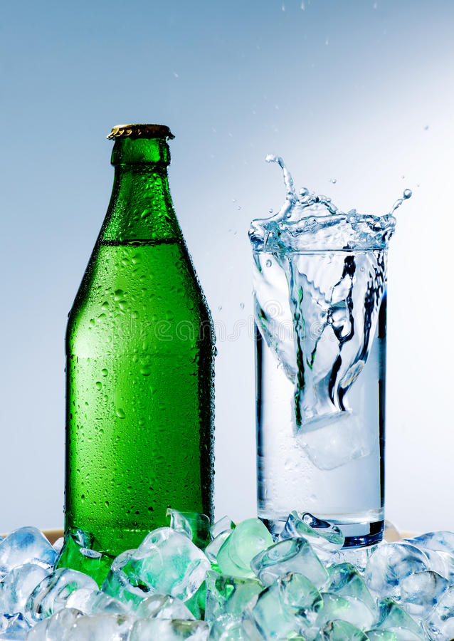 Bottle and glass with mineral water. A bottle of mineral water with ice and a glass on a blue background stock photo