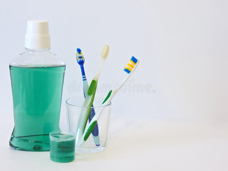Bottle and glass of mouthwash on bath shelf with toothbrush. Dental oral hygiene concept. Set of oral care products royalty free stock images