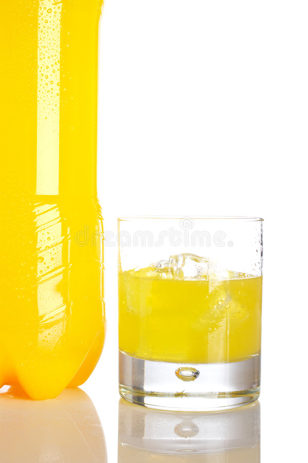 Bottle and glass of orange soda with droplets royalty free stock photography