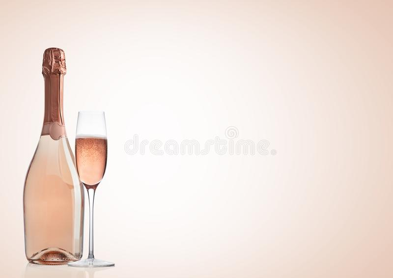 Bottle and glass of pink rose champagne on pink royalty free stock photo
