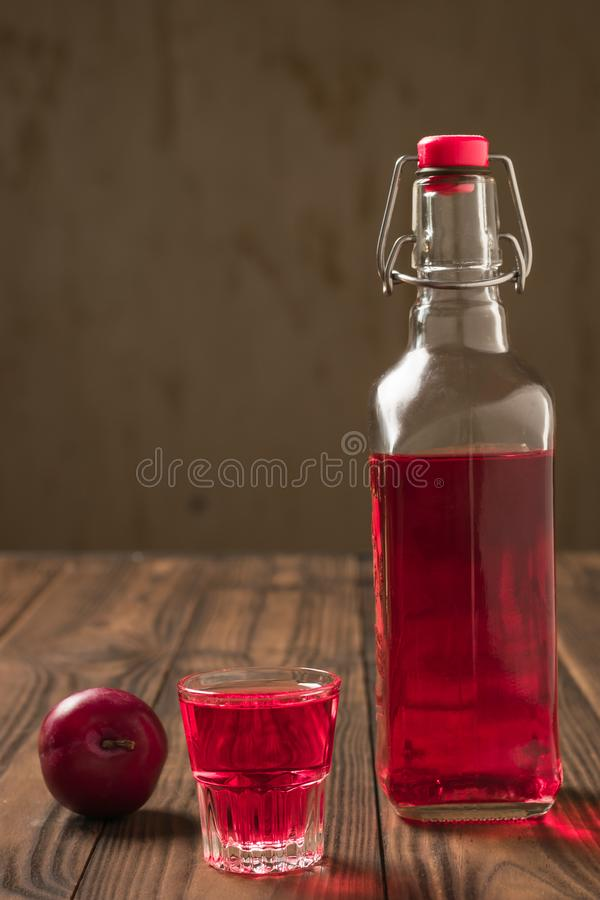 A bottle and a glass of plum alcohol on a wooden table. Homemade alcoholic drink made from berries plum royalty free stock image