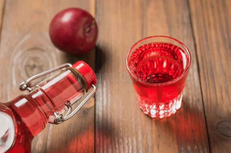 A bottle and a glass of plum liqueur on a wooden table. Flat lay. royalty free stock photography