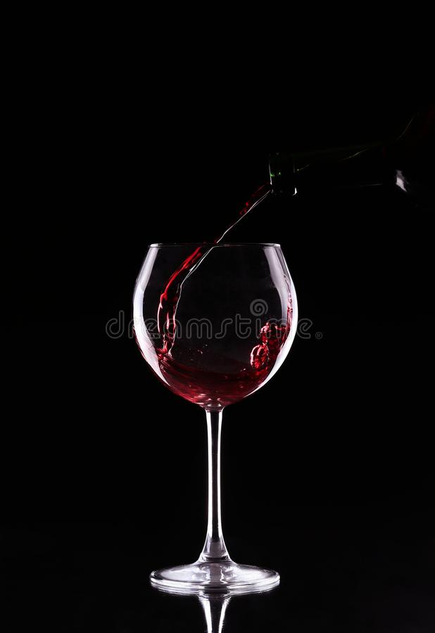 Bottle and glass with red wine on a black stock photography