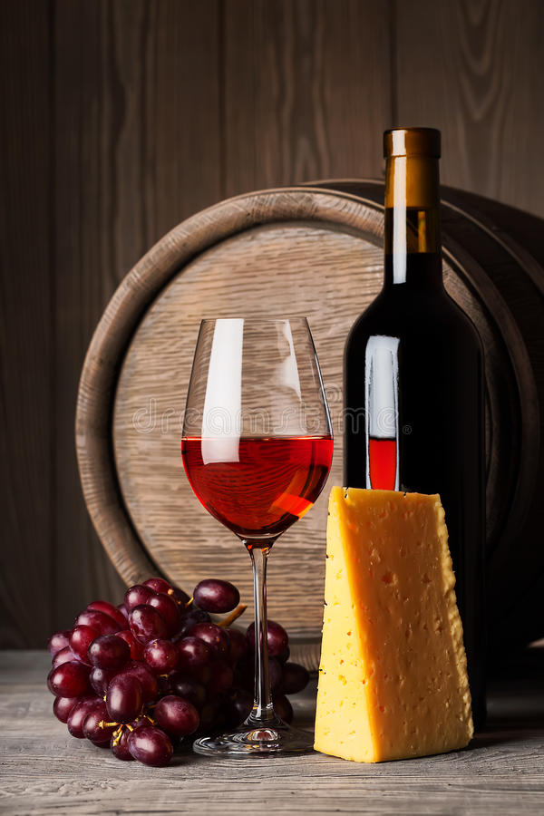 Bottle and glass of red wine with cheese and stock photos