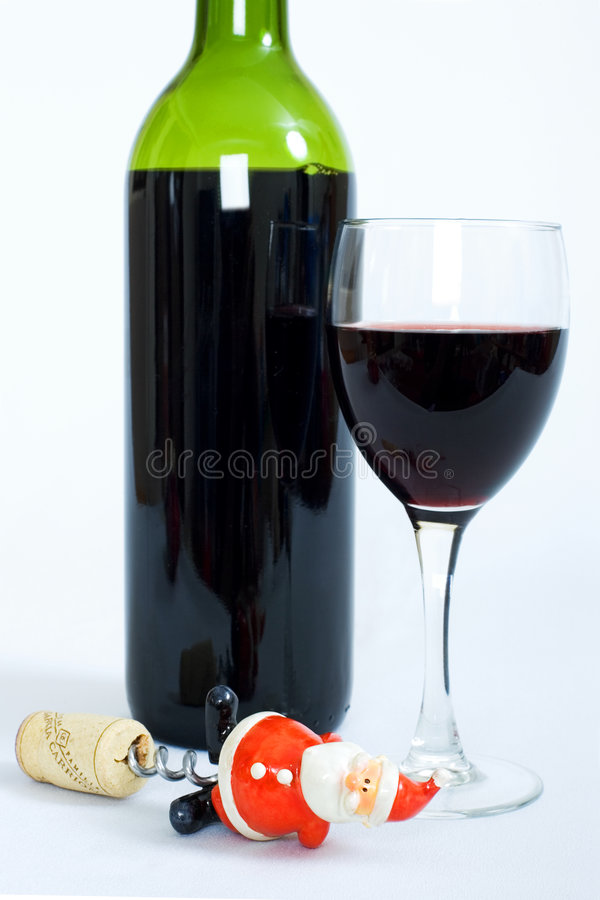 Bottle and glass of red wine with santa claus corkscrew royalty free stock photos