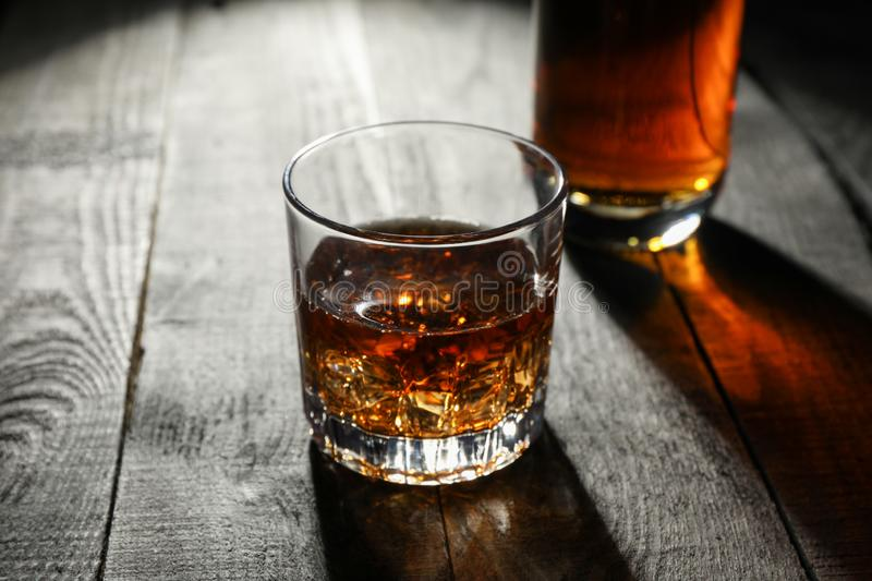 Bottle and glass of whiskey on wooden background stock photo