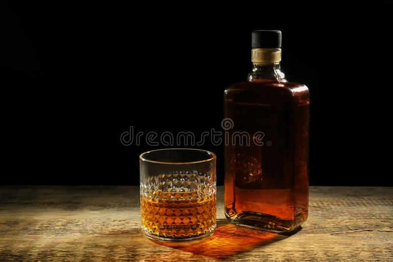 Bottle and glass of whiskey on wooden table against dark background stock photo