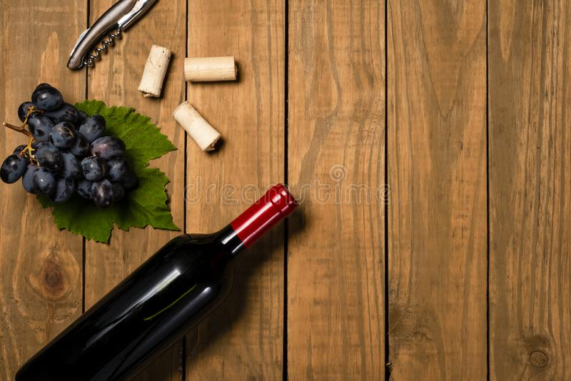 Bottle and glass with wine bunches of grapes and vine leaves on wooden background. Top view with copy space royalty free stock image