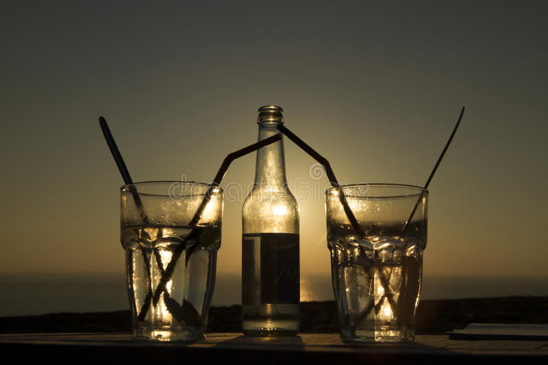Bottle and glasses. Backlight at sunset. One bottle and two glasses with soft drink at the backlight of the sunset over the Altalntic sea stock image