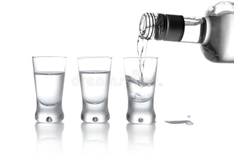 Bottle and glasses of vodka poured into a glass isolated on whit royalty free stock photos