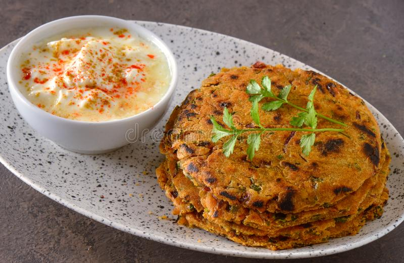 Lauki thepla and curd. Bottle gourd stuffed flatbread or lauki thepla served with yogurt dip stock photo