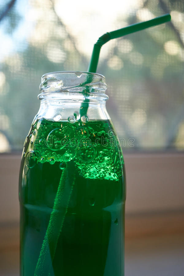 Bottle of green aerated water with straw. Bottle of green aerated water with drinking straw on pub desk stock image