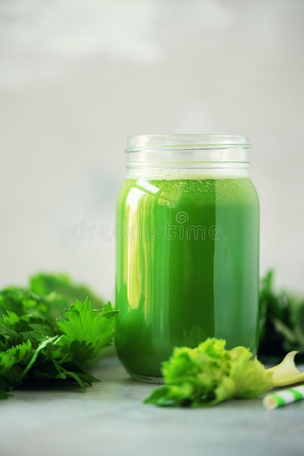 Bottle of green celery smoothie on grey concrete background. Banner with copy space. Square crop. Fresh juice for detox. Vegan, stock photography