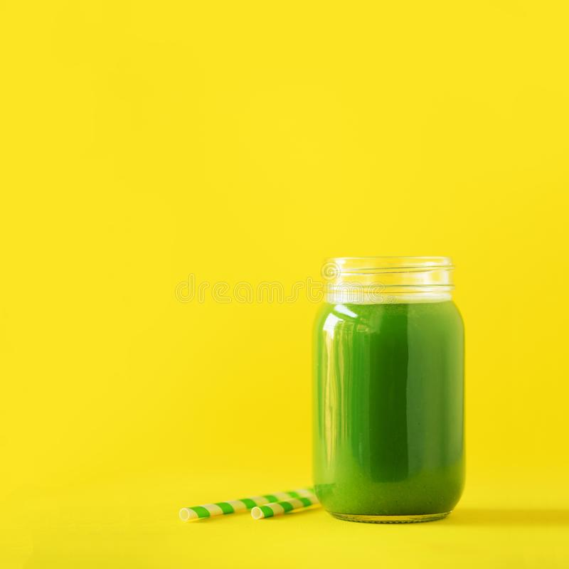 Bottle of green celery smoothie on yellow background. Banner with copy space. Square crop. Fresh juice for detox. Vegan, alkaline royalty free stock images