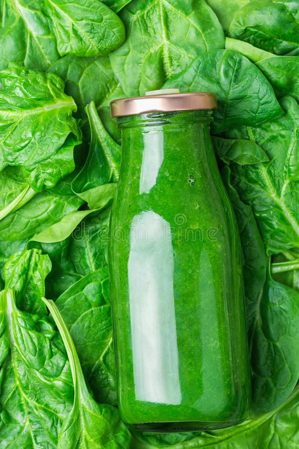 Bottle with Green Fresh Raw Smoothie from Leafy Greens Vegetables Fruits Apples Bananas Kiwi Zucchini on Spinach Leaves Background. Bottle with Green Fresh Raw stock images