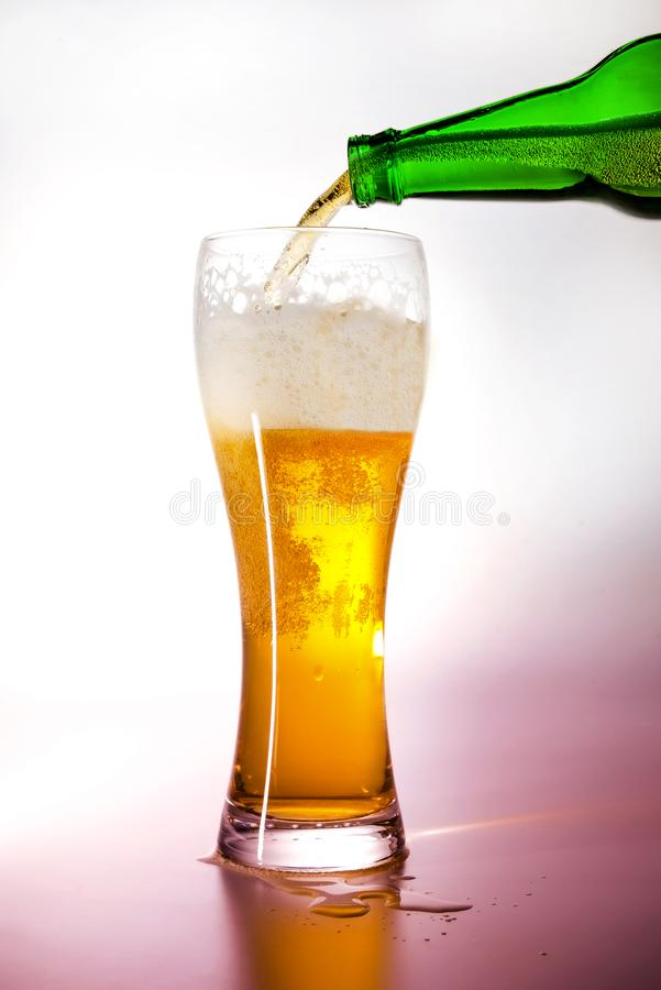 A bottle of green glass pouring beer into a beer glass. Background illumination with white light turning into light magenta. royalty free stock photo