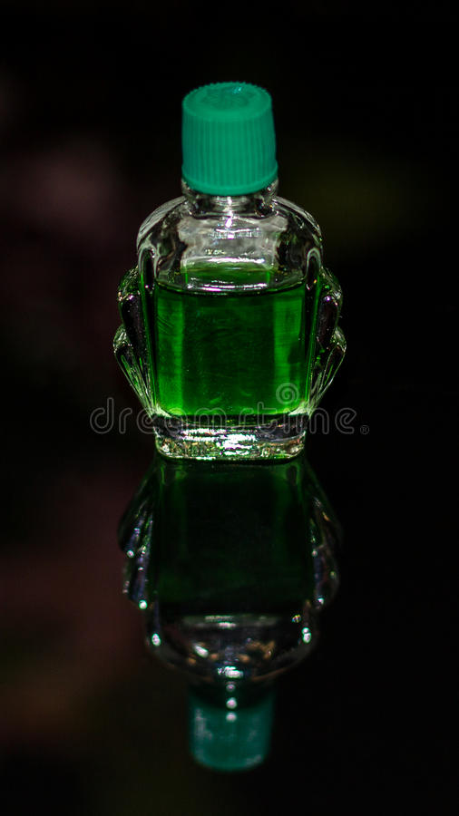 Bottle of Green Liquid. Similar to a traditional Chinese medicine called Feng You Jing. The green liquid is in a clear glass bottle with a plastic green top stock photo