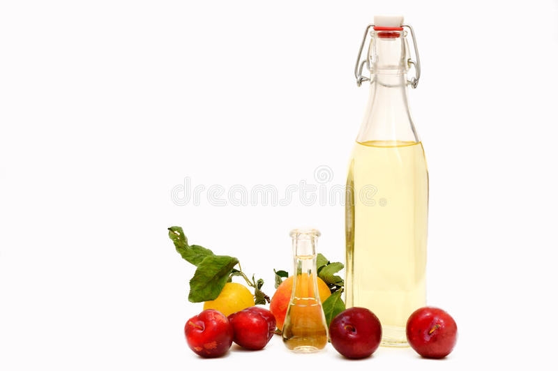 A bottle of homemade plum brandy with fresh plums. A bottle of homemade slavic plum brandy slivovits or slivovitz with some fresh plums on a white background royalty free stock image