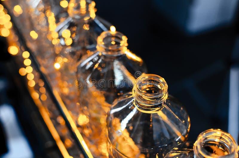 Bottle. Industrial production of plastic pet bottles. Factory line for manufacturing polyethylene bottles. Transparent food packag stock image