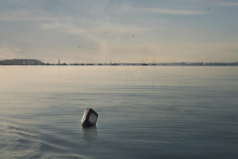Bottle with irritable contents polluting a beautif royalty free stock image