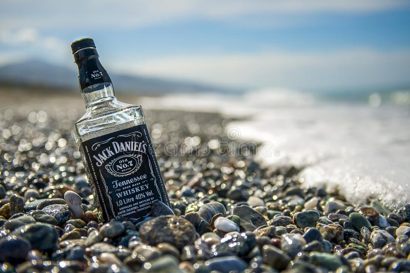 Bottle of Jack Daniels on stone beach stock photos