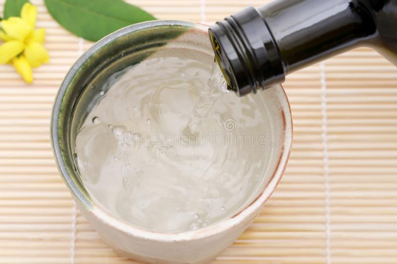 Bottle of Japanese shochu and ceramic bowl. On bamboo table stock photo