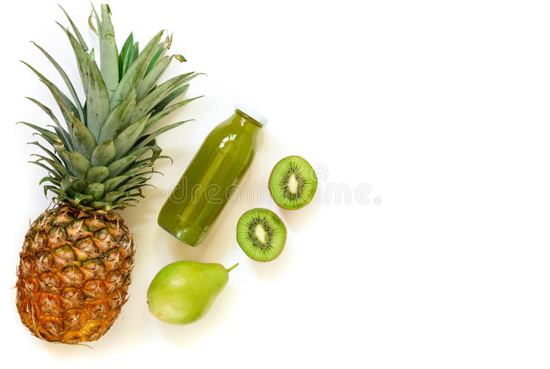 Bottle of kiwi, pineapple, pear juice isolated on white and ingredients. royalty free stock photography
