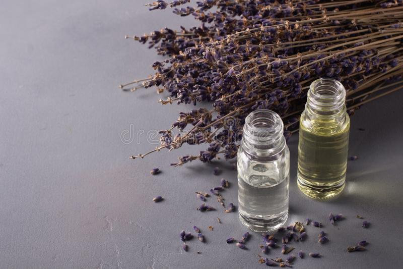 A bottle of lavender essential oil with blue flowers. Aromatherapy stock image