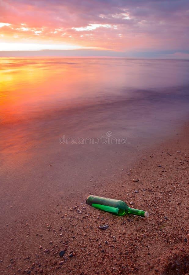 Bottle with message on sea coas stock photos