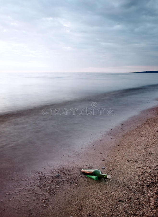 Bottle with message on sea coast royalty free stock image