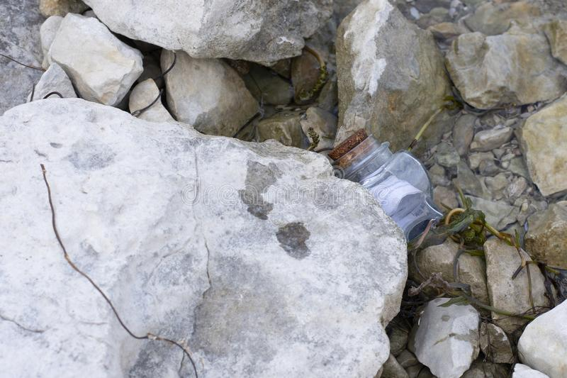 Message in bottle stuck under a rock royalty free stock photos