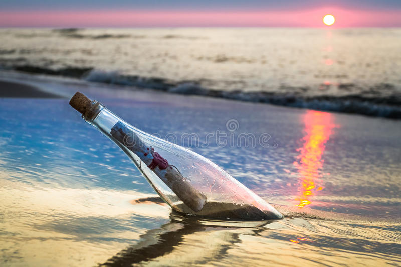 Bottle with a message thrown by the sea royalty free stock photos