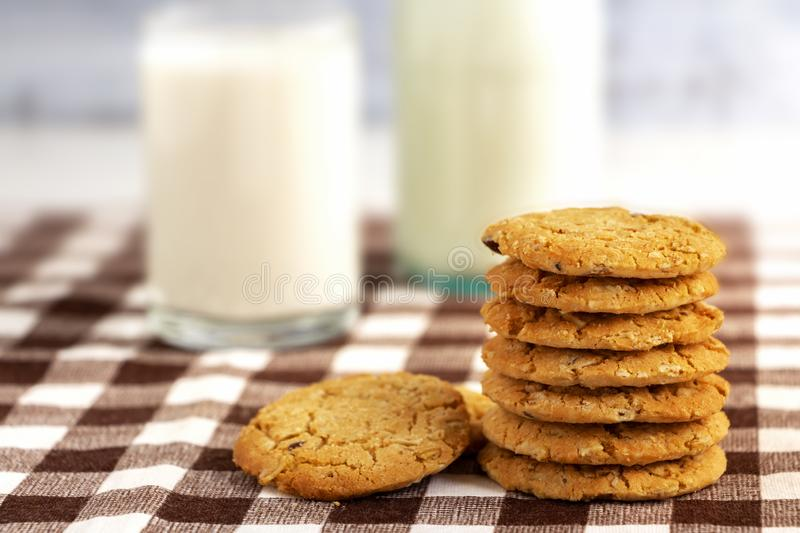 A bottle of milk and cookies made of oats on the wooden table. Copy space for your text or image stock images