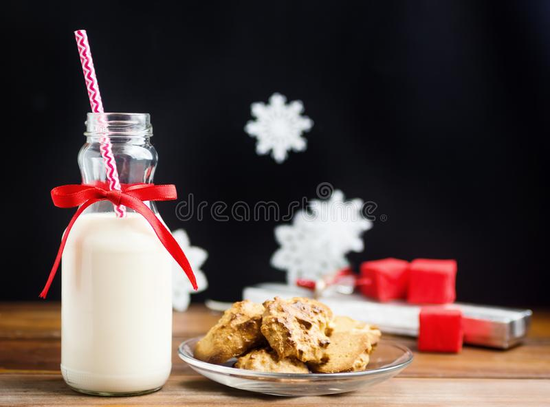 Bottle of milk with red ribbon and santas cookies on wooden table royalty free stock photography