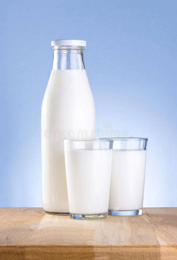 Bottle of milk and two glass is wooden table royalty free stock photos