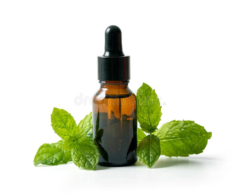 Bottle with mint essential oil and green leaf isolated on white background royalty free stock photos